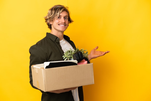 Blonde man making a move while picking up a box full of things isolated on yellow wall extending hands to the side for inviting to come