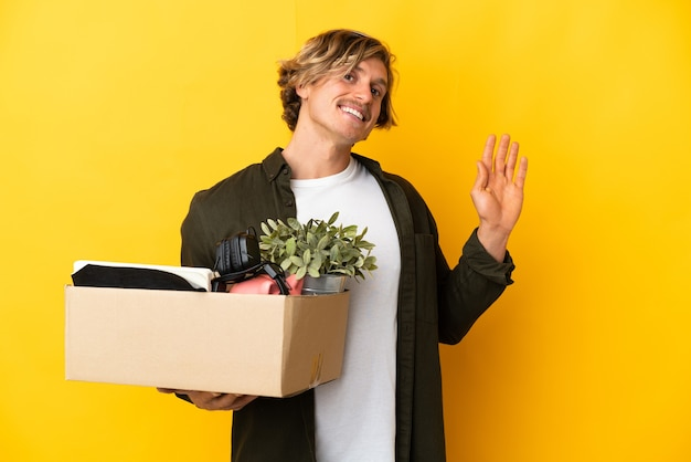 Blonde man making a move while picking up a box full of things isolated on yellow wall saluting with hand with happy expression