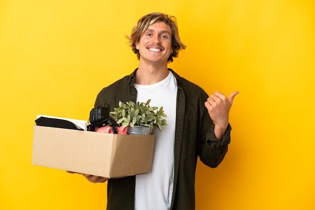 Blonde man making a move while picking up a box full of things isolated