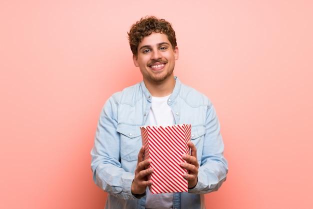 Blonde man over pink wall eating popcorns