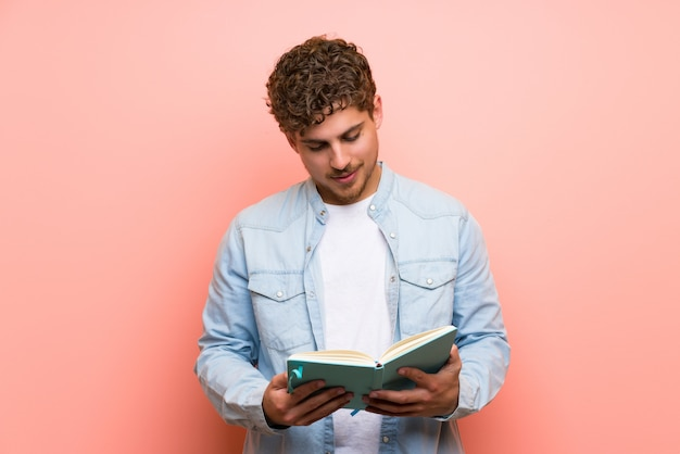 Blonde man over pink wall holding a book and enjoying reading