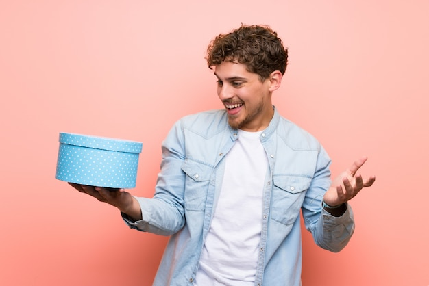 Blonde man over pink wall holding gift box in hands