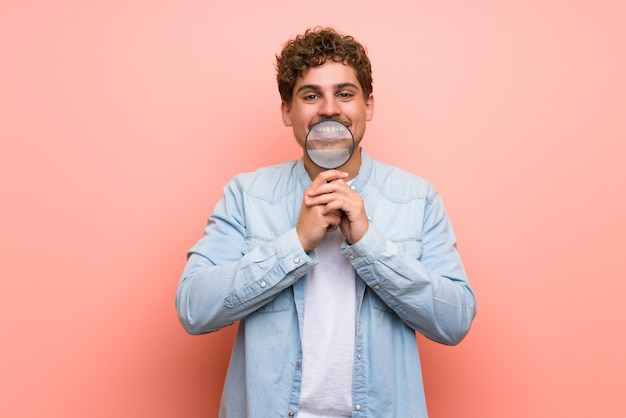 Blonde man over pink wall holding a magnifying glass