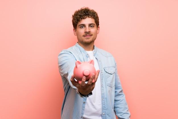 Blonde man over pink wall holding a piggybank