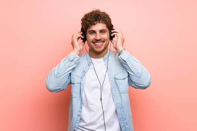 Blonde man over pink wall listening to music with headphones