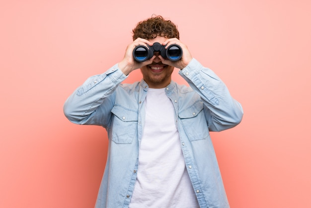 Blonde man over pink wall and looking in the distance with binoculars