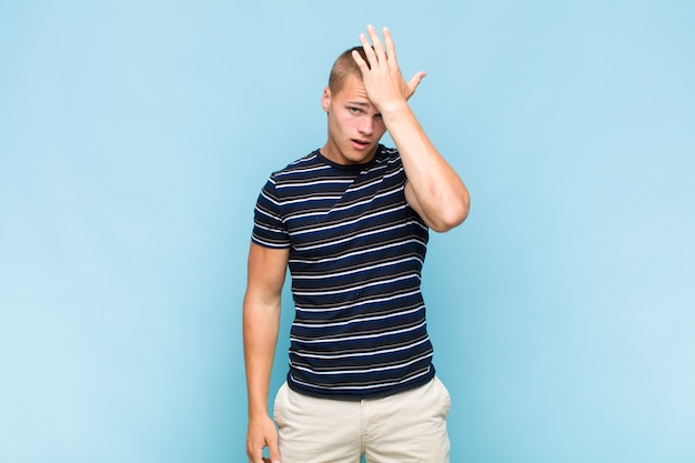 Blonde  man raising palm to forehead thinking oops, after making a stupid mistake or remembering, feeling dumb