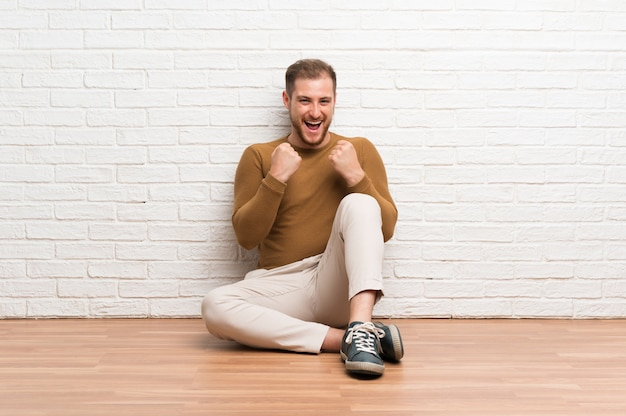 Blonde man sitting on the floor celebrating a victory