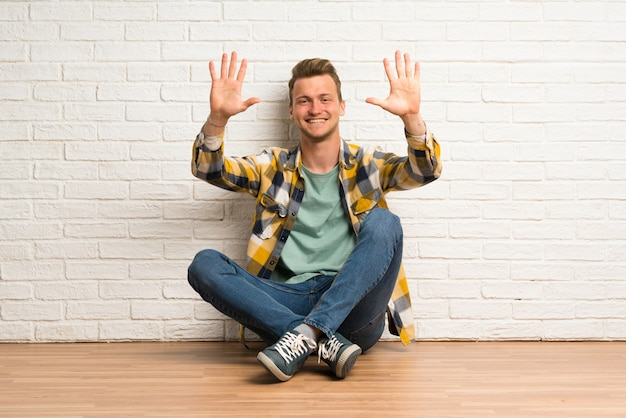 Blonde man sitting on the floor counting ten with fingers
