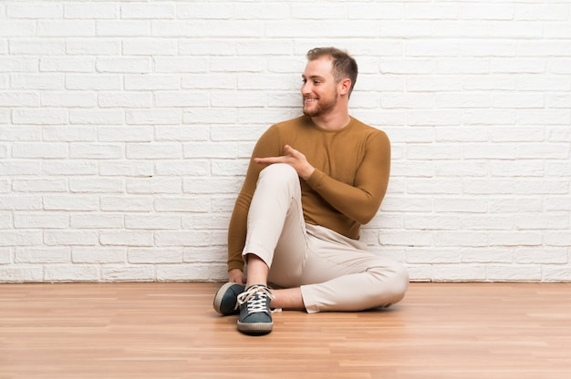 Blonde man sitting on the floor extending hands to the side for inviting to come