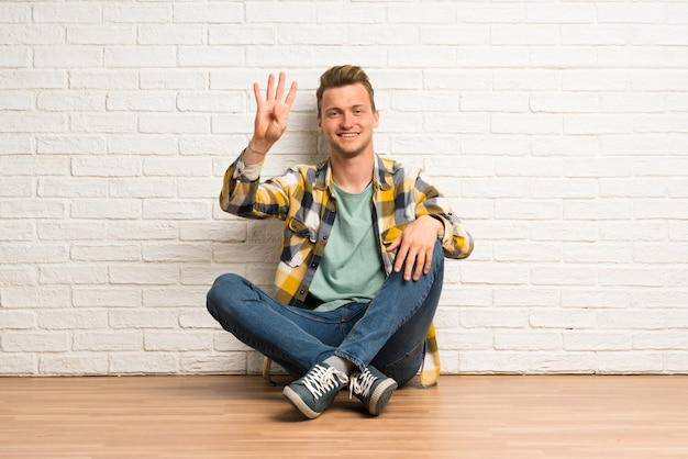 Blonde man sitting on the floor happy and counting four with fingers