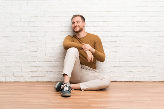 Blonde man sitting on the floor laughing and looking up