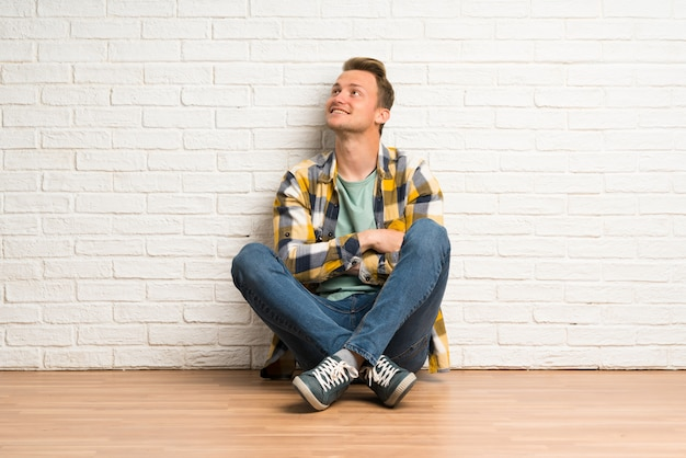 Blonde man sitting on the floor looking up while smiling