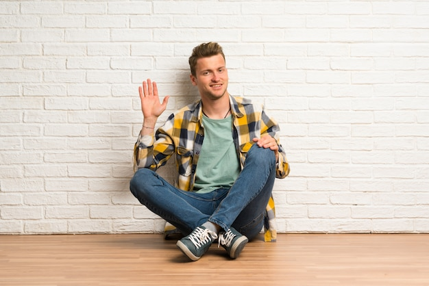 Blonde man sitting on the floor saluting with hand with happy expression