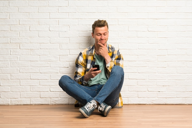 Blonde man sitting on the floor thinking and sending a message