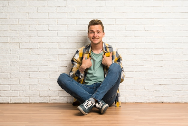 Blonde man sitting on the floor with surprise facial expression