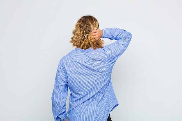 생각하거나 의심하는 금발의 남자, 머리를 긁적, 의아해하고 혼란스러워하는 느낌, 뒤로 또는 후면보기