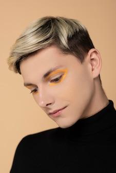 Blonde man wearing orange eyeliner