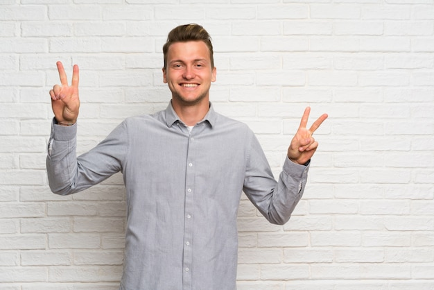 Blonde man over white brick wall showing victory sign with both hands