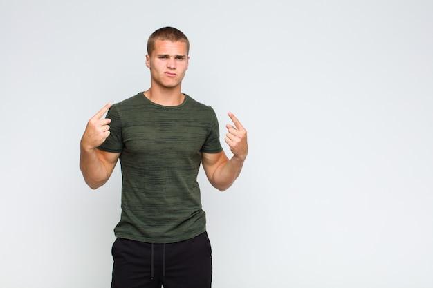 Светловолосый мужчина с плохим настроем выглядит гордым и агрессивным, указывая вверх или весело жестикулирует руками