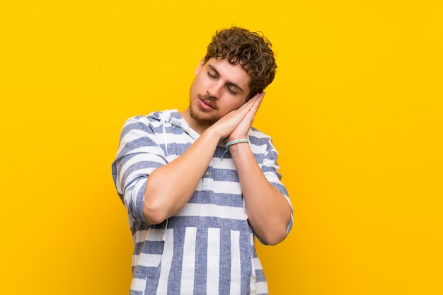 Blonde man over yellow wall making sleep gesture in dorable expression