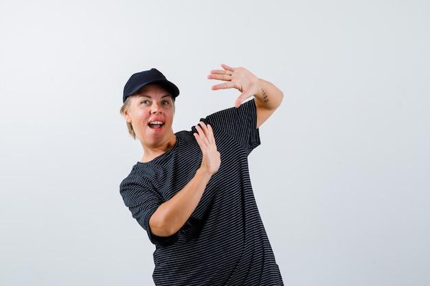 Donna matura bionda in una maglietta nera e un berretto nero