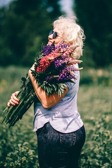 Blonde mature woman holding a lupine bouquet on nature.