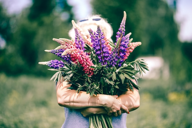 Blonde mature woman holding a lupine bouquet on nature