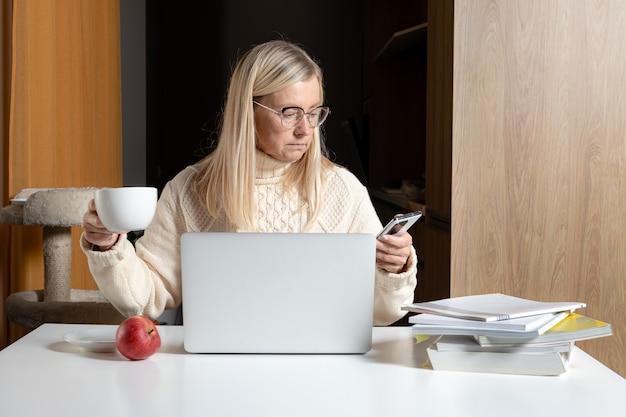 Блондинка средних лет бизнесвумен сидит за столом, пьет чай и работает с ноутбуком из домашнего офиса