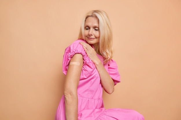 La bionda donna europea di mezza età guarda il suo braccio vaccinato riceve un'iniezione di vaccino indossa un abito rosa isolato su una parete beige