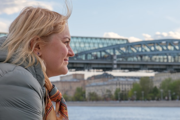 Blonde middleaged woman in profile stands on embankment and looks at river against the background of city bridge. wind develops the womans hair.