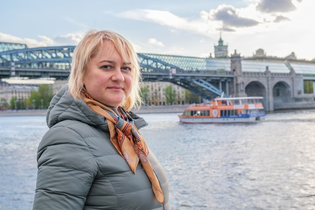 Blonde middleaged woman stands on embankment and looks at camera against the background of city bridge. concept city walks, sightseeing, travel