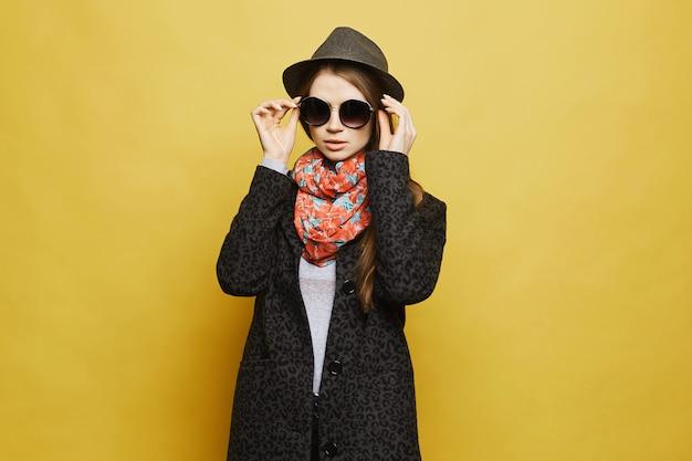 トレンディな帽子とサングラスのポーズで、スタイリッシュなコートで金髪のモデルの女の子。テキスト用のスペースをコピーします。