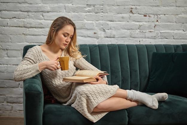 ベージュのニットドレスと靴下の金髪モデルは、灰色のソファに寄りかかって、茶色のカップを持って、白いレンガの壁に本を読んでいます。週末、学生、ブロガー、ドキュメントの勉強。閉じる