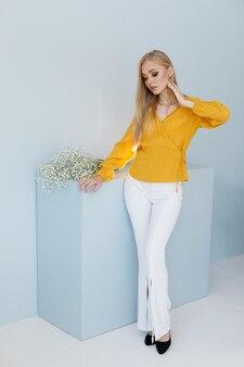 Блондинка модель в стильной одежде на синем фоне. плакат. покупки онлайн
