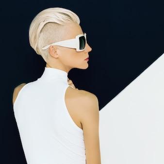 세련된 이발과 트렌디한 선글라스를 쓴 금발 모델. 패션 사진