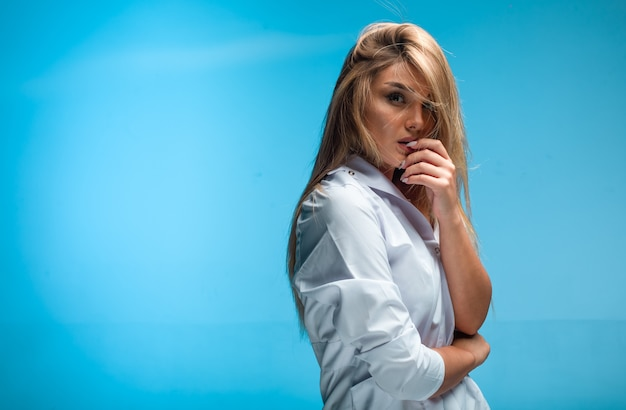 白いシャツの金髪モデルは情熱的に見えます。