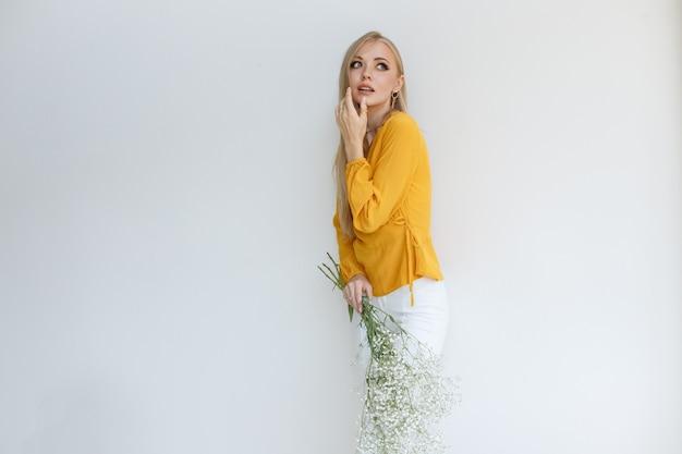 花と灰色の背景に明るい化粧の金髪モデル。テキスト用の空き容量