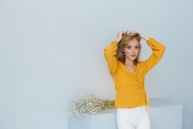 ファッショナブルな背景に長い健康な髪を持つブロンドのモデルは彼女の髪に触れます