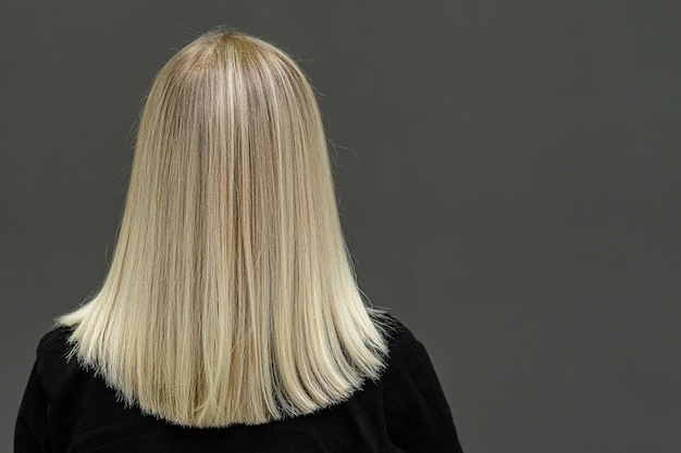 ストレートヘアの金髪モデル、後ろから見てください。髪を明るくする結果。コピースペース