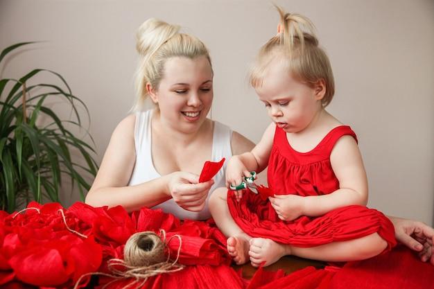 금발 엄마와 딸이 집에서 테이블에 앉아 붉은 종이 꽃을 만듭니다. 고품질 사진