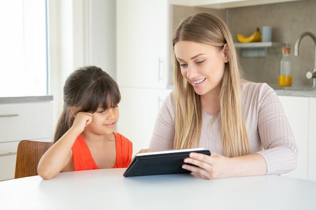 タブレットを押しながら娘に見せている金髪のお母さん。