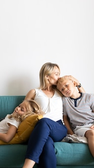 金髪のお母さんが息子の頭にキスをし、ソファの空白スペースで娘とリラックス