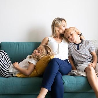 金髪のお母さんが息子の頭にキスをし、ソファで娘とリラックス