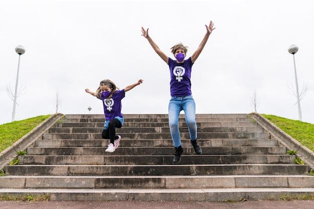 3月8日の国際女性デーに働く女性のシンボルが付いた紫色のtシャツを着て、コロナウイルスのマスクを身に着けて通りの階段にジャンプする金髪の母と娘