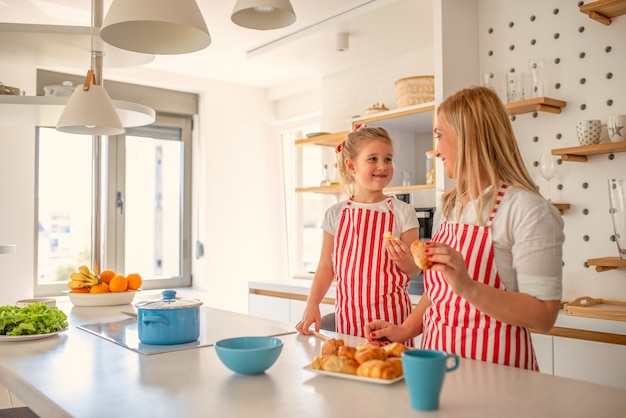 Blonde mother and daughter cooking together happily