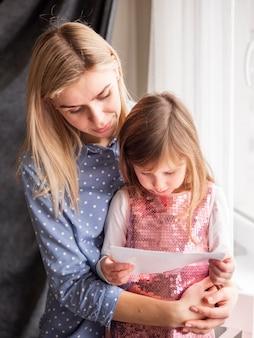 Блондинка мама держит маленькую дочь