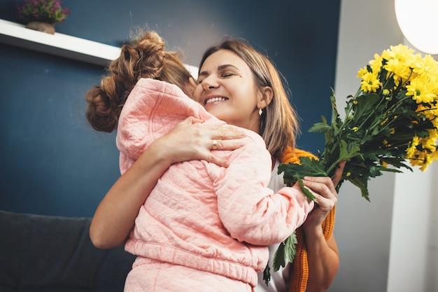 금발의 어머니는 어머니의 날에 그녀로부터 꽃을받은 후 딸을 껴안고 있습니다.