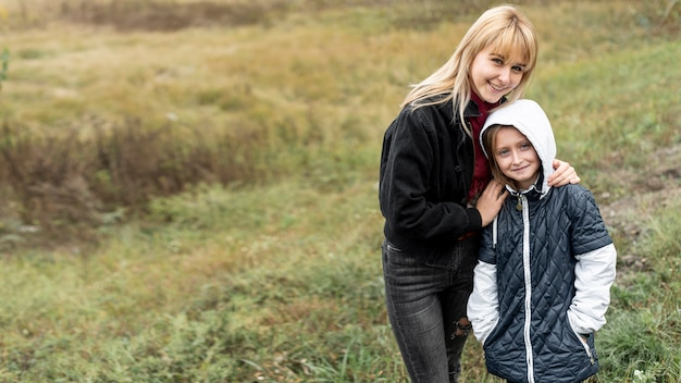 Blonde mother and little girl posing in nature