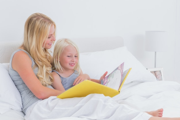 Blonde mother reading a story to her daughter